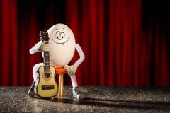 怂恿吉他弹奏者坐与吉他的一把椅子 免版税图库摄影