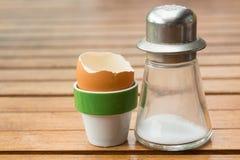 怂恿持有人和盐瓶用一个被吃的鸡蛋 免版税图库摄影