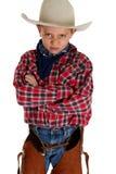 怒视照相机佩带的帽子和破裂双臂的年轻牛仔被交叉 免版税库存照片