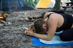 思考与卡利市mudra手瑜伽姿势的少妇,当野营在森林里时 图库摄影