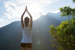 思考在山峰峭壁边缘的瑜伽妇女 免版税库存照片