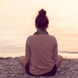 思考在平静的海滩日落的妇女 库存图片