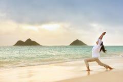 思考在战士姿势的瑜伽妇女在海滩 免版税库存照片