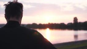思考在日出的慢动作自由的人 的周道的男性享受平安的早晨水全景的后面观点 股票录像