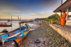 思考在日出的泰国修士在港口 免版税库存照片