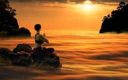 思考在日落的瑜伽妇女 库存照片
