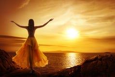 思考在日落的镇静妇女,在开放胳膊姿势放松 免版税库存照片