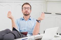 思考在有他的腿的办公室的商人在书桌 免版税库存图片