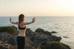 思考在海滩的女孩在日落 图库摄影