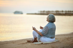 思考在海滩的成熟妇女 图库摄影