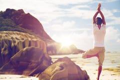 思考在瑜伽在海滩的树姿势的人 免版税库存图片