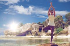 思考在瑜伽在海滩的树姿势的妇女 免版税库存图片