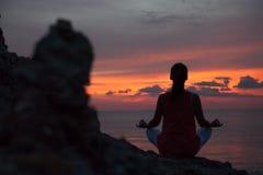 思考在瑜伽姿势的妇女在海滩 图库摄影
