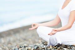 思考在瑜伽姿势的妇女的手在海滩 免版税库存照片