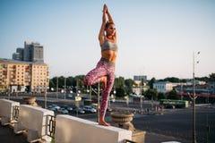 思考在瑜伽姿势,平衡锻炼的妇女 库存照片