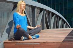 思考在瑜伽莲花姿势的城市中央公园的妇女 体育,健身,活跃生活方式,都市锻炼概念 免版税图库摄影