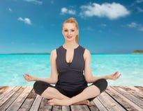 思考在瑜伽莲花姿势的愉快的少妇 免版税库存照片