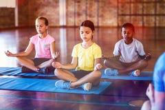 思考在瑜伽类期间的学校孩子 免版税库存图片