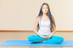 思考在瑜伽锻炼前的被启发的亚裔妇女室内 库存图片