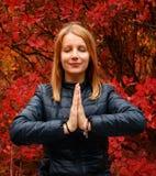 思考在秋天森林里的女孩 免版税库存图片