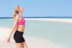 思考在美丽的海滩的妇女 库存照片