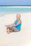 思考在美丽的海滩的资深妇女 免版税库存图片