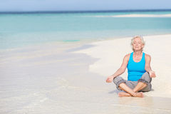 思考在美丽的海滩的资深妇女 免版税图库摄影
