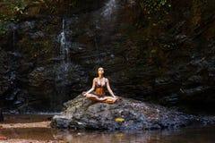 思考在自然瀑布的妇女在岩石在森林里 免版税库存图片