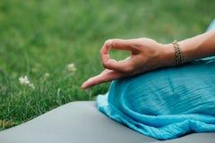 思考在莲花坐特写镜头的妇女 递特写镜头mudra 坐地毯绿草背景草坪  库存图片