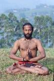 思考在莲花瑜伽姿势的印地安人在绿草在Keral 免版税库存照片