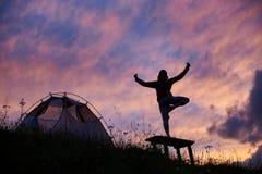 思考在长凳的女性登山人在山坡的帐篷附近在罗马尼亚 库存照片