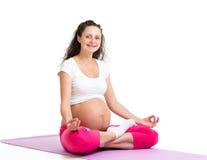 思考怀孕的瑜伽的妇女放松和 免版税库存照片