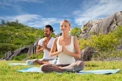 思考愉快的夫妇做瑜伽和户外 免版税库存图片