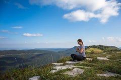 思考或做瑜伽,当坐与不可思议的山风景时的岩石上面,健康生活方式的少妇 库存图片