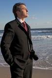 思考海滩的生意人 免版税库存照片