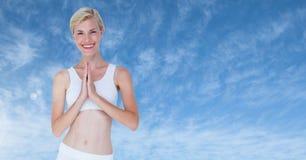 思考由蓝色云彩的女子祈祷的瑜伽 库存图片