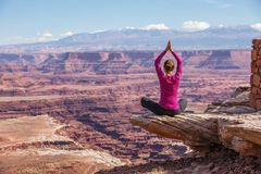 思考的妇女做瑜伽在Canyonlands国家公园在犹他 免版税库存照片