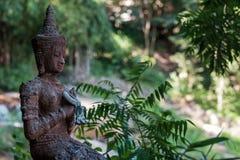 思考的菩萨的一个古老雕象反对一个绿色森林或密林的背景的 库存照片
