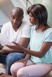 急切夫妇坐他们的付他们的帐单的长沙发 免版税库存照片