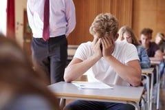 急切少年学生坐的考试在学校霍尔 免版税库存照片