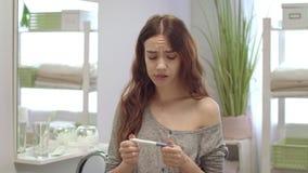 急切年轻女人在卫生间里看结果怀孕的测试 无计划的怀孕 股票录像