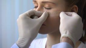 急救测量,把补丁放的医生在受伤的女性耐心面孔,特写镜头上 影视素材