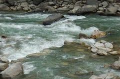 急流在一条山河在尼泊尔 免版税库存照片