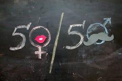 性别标志或标志在黑板和女性的画的男性 免版税图库摄影