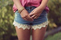 性感和有吸引力的妇女腿和手,佩带的性感的偶然牛仔布短裤 免版税库存图片