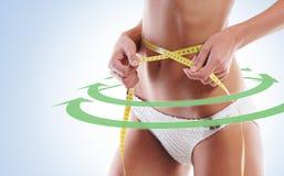 性感和适合的femaly身体 妇女测量她的腰部 免版税图库摄影