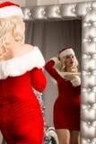 性感圣诞节女孩摆在 作为圣诞老人打扮的白肤金发的妇女站立在镜子前面 免版税库存图片