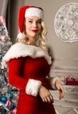 性感圣诞节女孩摆在 作为在照相机前面的圣诞老人打扮的白肤金发的妇女 库存图片