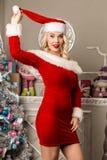 性感圣诞节女孩摆在 作为在照相机前面的圣诞老人打扮的白肤金发的妇女 免版税库存图片