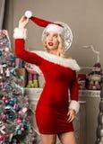 性感圣诞节女孩摆在 作为在照相机前面的圣诞老人打扮的白肤金发的妇女 免版税图库摄影